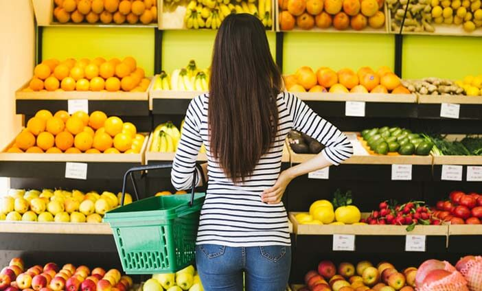 Woman Standing in front of produce