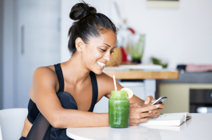 Woman in fitness clothes sitting at table drinking smoothie looking up info on her phone