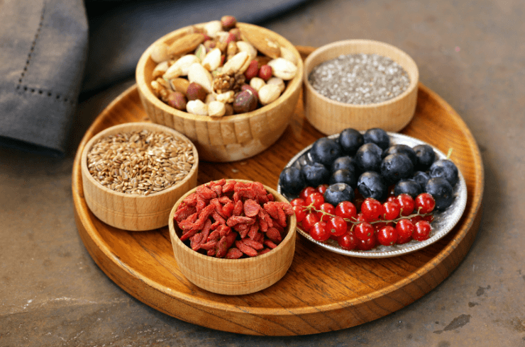wood tray with cup of nuts seeds and berries
