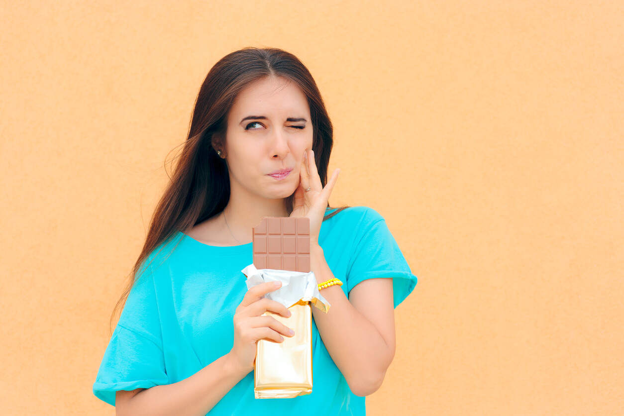 Girl eating chocolate bar with tooth ache