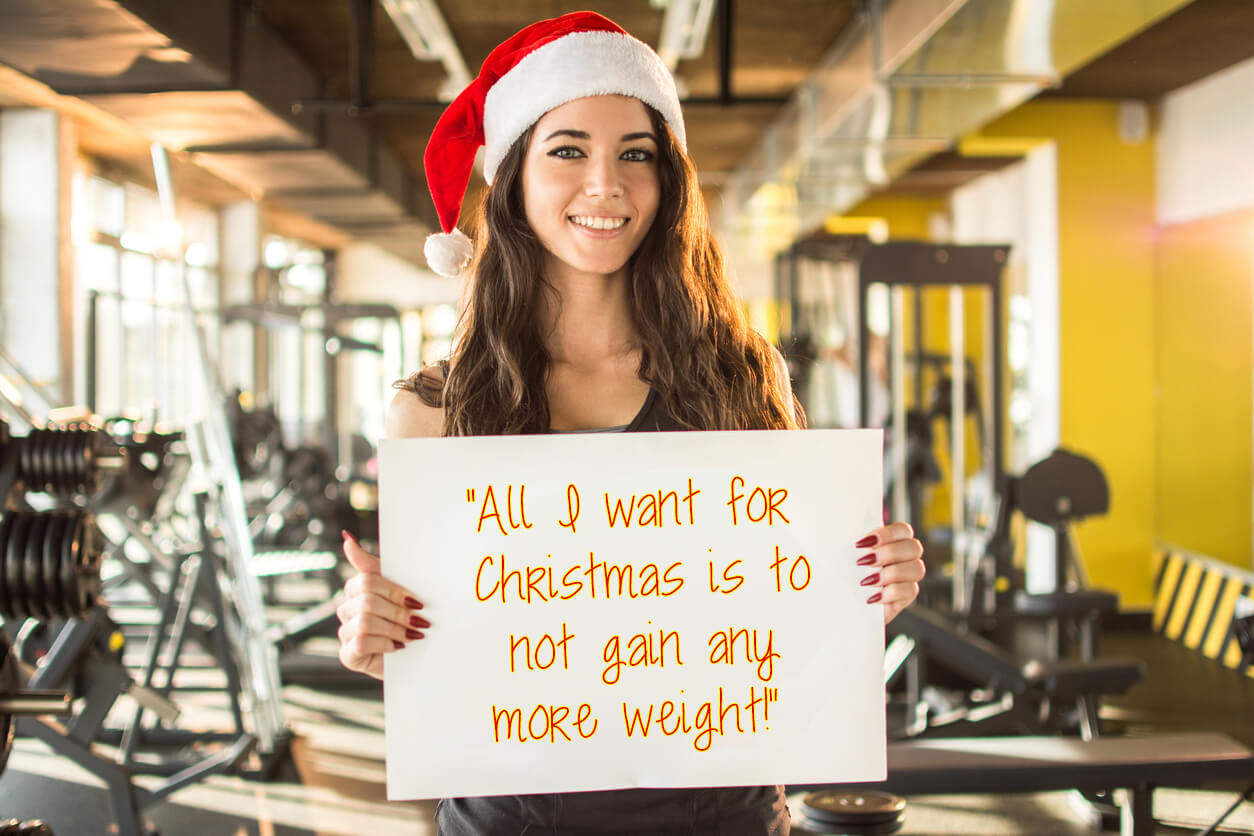 "Woman holding a ""All I want for Christmas is to not gain weight"" sign"