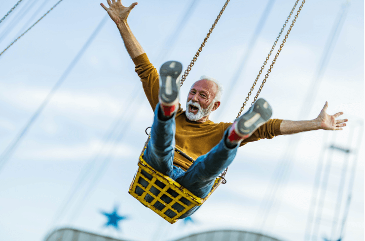 Happy Mature man having fun on chain swing ride at amusement park