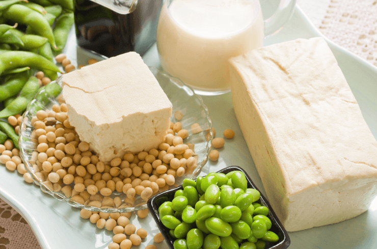 Full block of tofu. Half block of tofu sitting on plate of loose soy beans. Green beans in black square bowl. Glass filled with soy milk 1