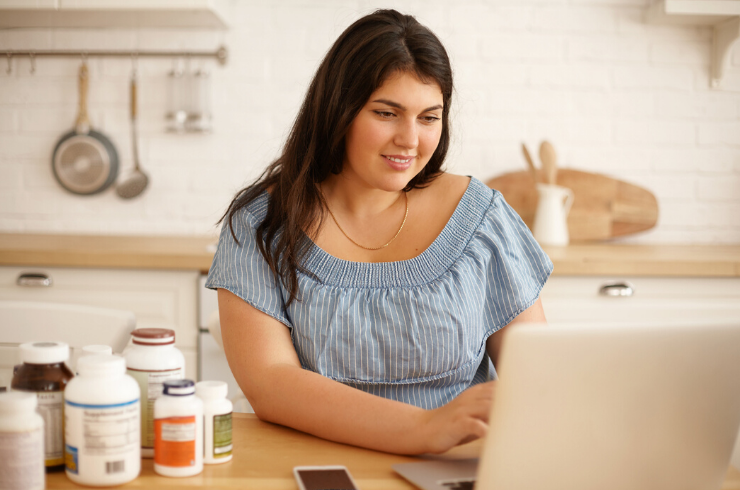Plus Woman At Laptop With Multiple Supplements