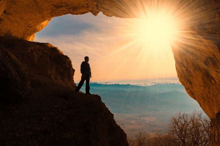 silhouette of man standing in a cave looking at sunset